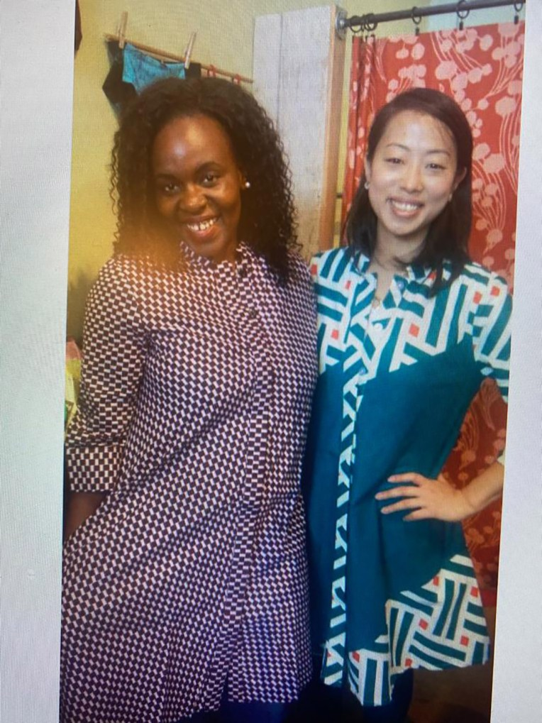 Two students pose wearing elaborately patterned shirt dresses