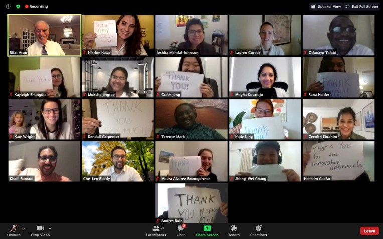 """A bunch of students in a zoom meeting hold up signs that say """"Thank you"""" for professor Rifat Atun"""