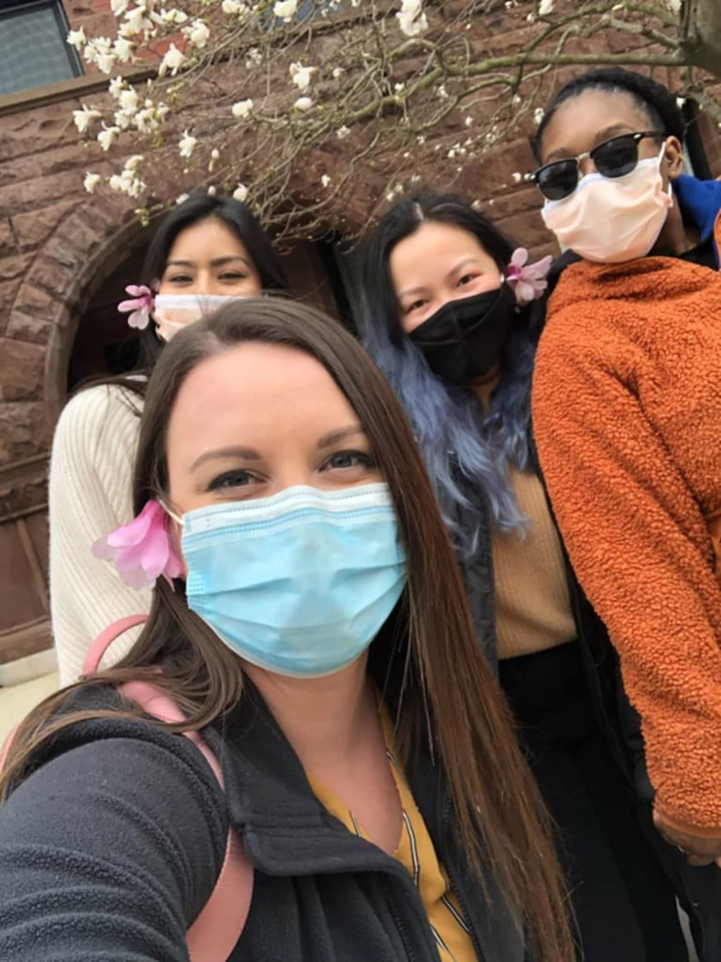 four students pose outdoors with masks on