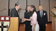 Dean Frenk shakes hands with Volunteer Leadership Award scholar Wen Xie as Deeda Blair and Maurice Tempelsman look on.