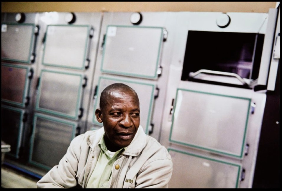 Botswana - Moses Selebogo has worked in the Princess Marina Hospital morgue since 1987. At the height of the AIDS crisis in Botswana, the morgue was always filled to capacity. He now measures the success of the country's AIDS treatment program by the vacancies at the morgue. On the day this photograph was taken, all the drawers were empty. ©Dominic Chavez