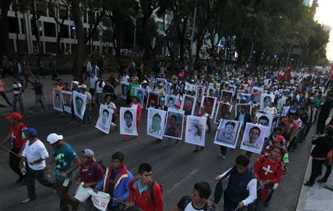 Relatives holding posters with images of the missing students march in protest for the disappearance of 43 students in the state of Guerrero, in Mexico City, Wednesday, Nov. 5, 2014.