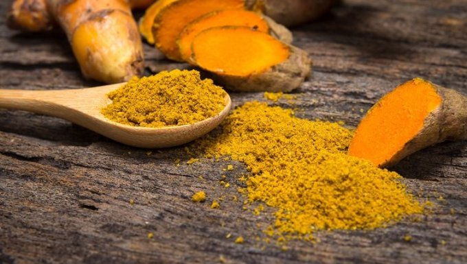 the turmeric powder in spoon and roots on wooden plate