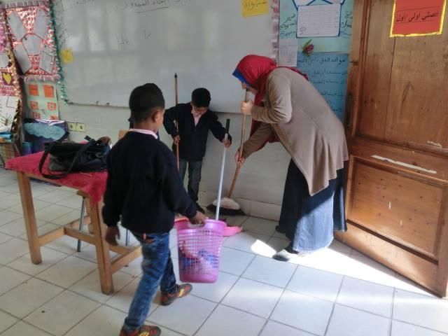 Dos niños barren un salón de clases ayudados por una mujer mayor.