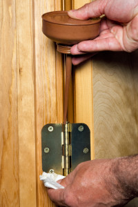 Oiling the hings of a door using an oil can