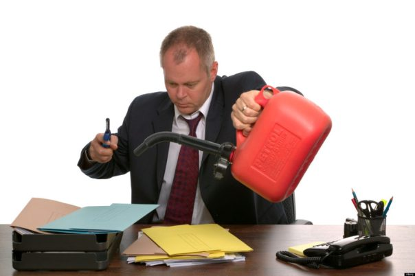 AJT6JK Businessman about to set fire to a pile of documents