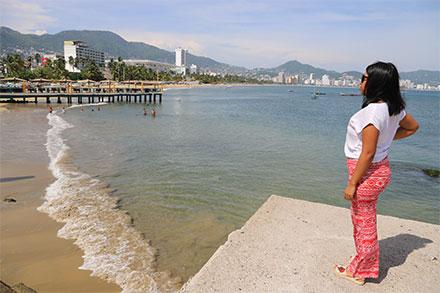Mujer observa la playa sucia