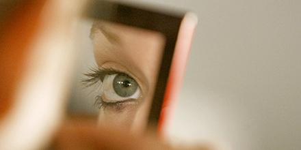 Mujer viendo su ojos frente a un espejo