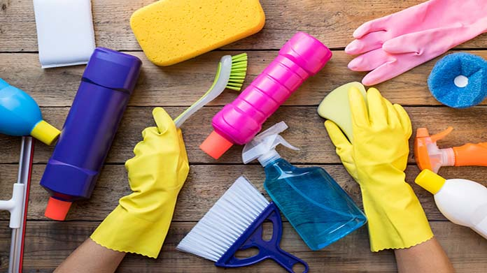 A pair of hands in rubber gloves and a desk full of cleaning supplies