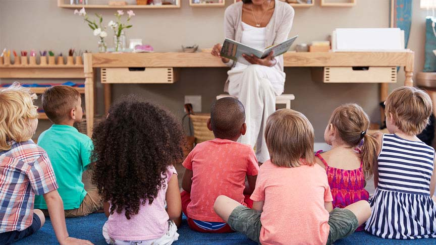 Woman reading to a group of children in a classroom or daycare setting