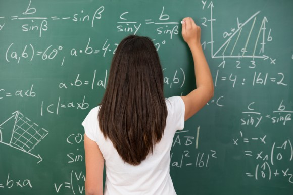 Clever young woman solving a mathematical problem standing with her back to the camera writing on a college blackboard