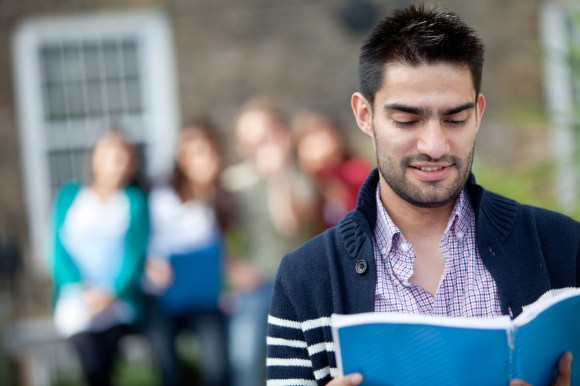Student with a notebook outdoors with a group of people at the background