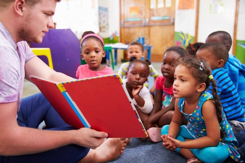 bigstock-Volunteer-teacher-reading-to-a-98584391