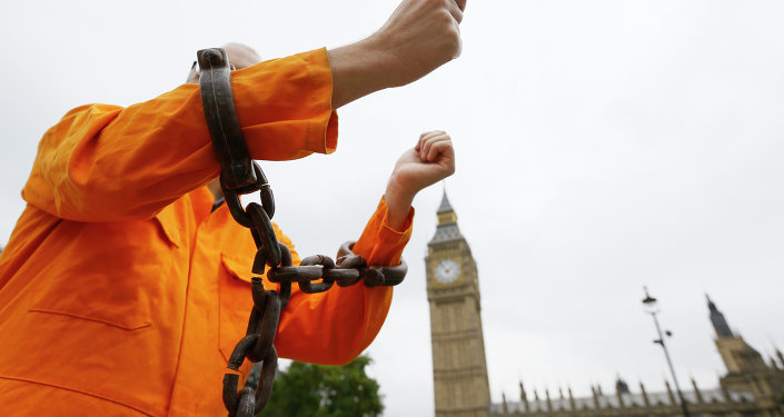 A protester holds up his chained arms during a protest against the Guantanamo Bay detention camp, in Parliament Square in London, Wednesday, Oct. 15, 2014