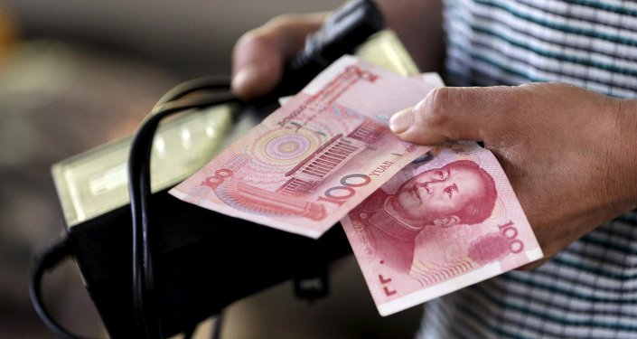 A customer holds a 100 Yuan note at a market in Beijing, August 12, 2015