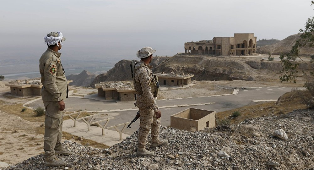 Shi'ite fighters look at former Iraqi president Saddam Hussein's palace at Makhoul mountains, north of Baiji, October 17, 2015
