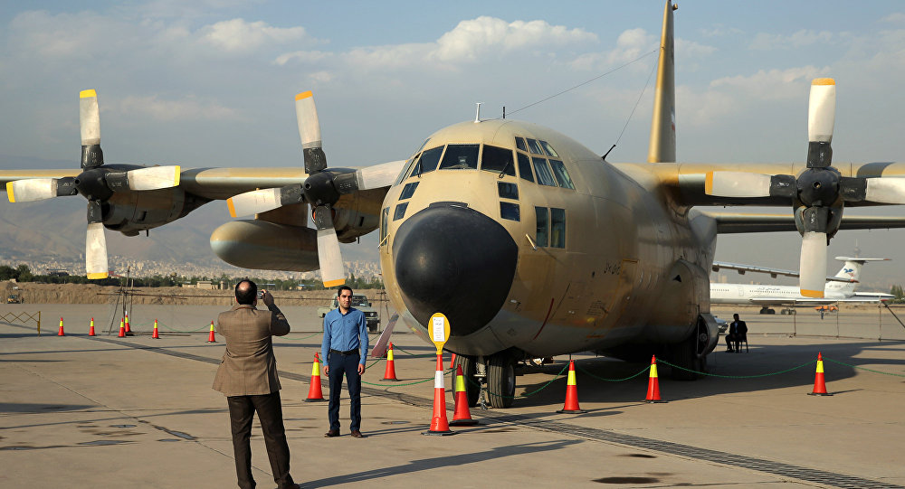 Iranians take pictures in front of a C-130 plane in an exhibition of achievements and equipment of Iran's air force in Tehran, Iran, Wednesday, Sept. 23, 2015