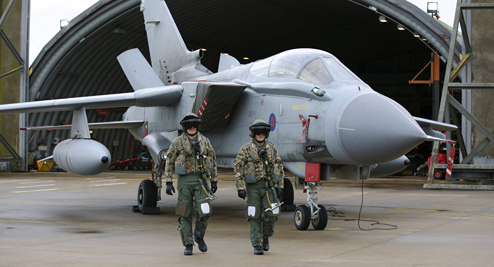Pilots walk in front of a Tornado GR4 aircraft at the British Royal Air Force airbase RAF Marham in Norfolk in east England on December 2, 2015.