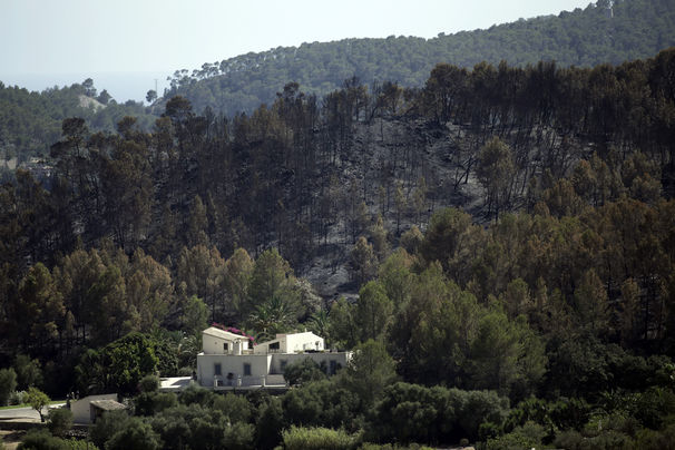 A helicopter works above a fire, near the village of Andratx on the Spanish Balearic island of Mallorca, Spain, Sunday, July 28, 2013. The regional government of Spain's Balearic Islands says a wildfire is raging out of control in Mallorca, the popular Mediterranean luxury tourist destination. A statement says some 700 residents had to be evacuated early Sunday morning from the village of Estallencs as fires fanned by winds spread eastward along wooded hills. (AP Photo/Manu Mielniezuk)