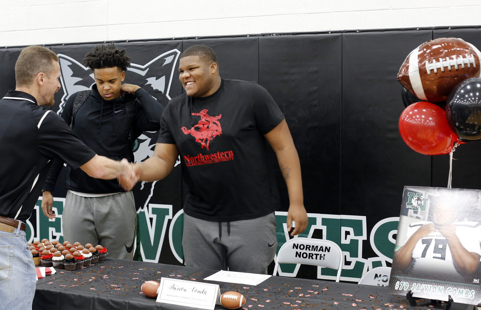 Photo - Senior Ja'Vion Combs, right, smiles while  greeting classmates, coaches and friends before signing a letter to play football with Northwestern Oklahoma State University during Signing Day event at Norman North High School on Wednesday, Feb. 6, 2019.  Photo by Jim Beckel, The Oklahoman.