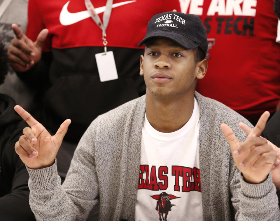 Photo - Titans football standout Dadrion Taylor makes the pistols gesture with his hands after he signed letter to play football with Texas Tech University during Signing Day ceremony at Carl Albert  High School on Wednesday, Feb. 6, 2019.  Photo by Jim Beckel, The Oklahoman.