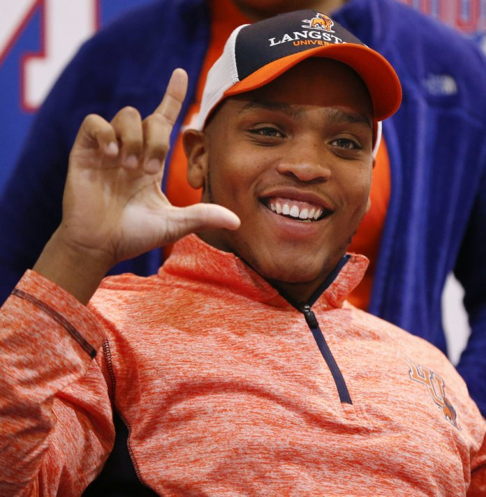 Photo - Millwood's Chase Coleman makes an L with his hands for Langston during the signing ceremony for high school football players in the Millwood Field House in Oklahoma City, Wednesday, Feb. 6, 2019. Coleman will play football at Langston. Photo by Nate Billings, The Oklahoman