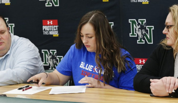 Photo - Alex Martin signs letter to play softball at Kansas City Kansas Community College during Signing Day event at Norman North High School on Wednesday, Feb. 6, 2019. Her parents are seated at the table with her.  Photo by Jim Beckel, The Oklahoman.