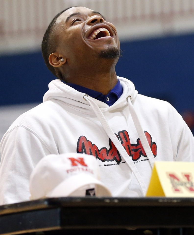 Photo - Millwood's De'Mariyon Houston laughs while listening to one of his teammates, who was also signing a letter of intent, speak during a signing ceremony for high school football players in the Millwood Field House in Oklahoma City, Wednesday, Feb. 6, 2019. Houston will play football at Nebraska. Photo by Nate Billings, The Oklahoman