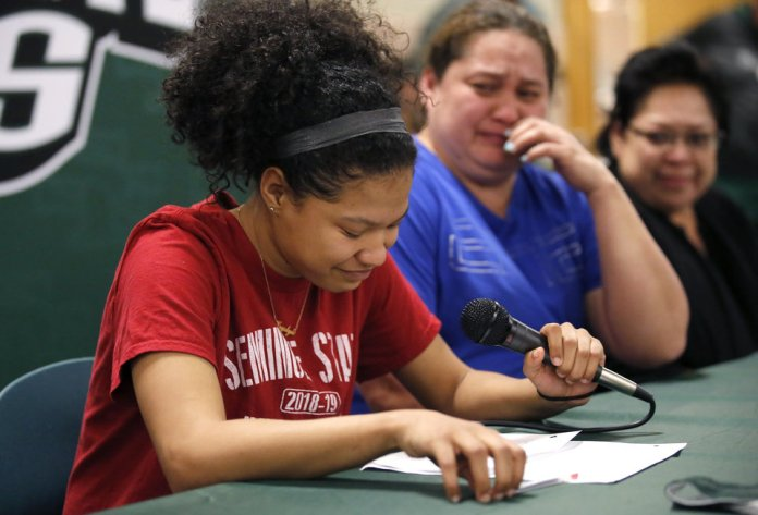 Photo - Kryslyn Jones reacts while speaking before signing to play basketball with Seminole State as her mom, Kerri Jones, reacts next her during signing day ceremony at Edmond Santa Fe High School in Edmond, Okla., Wednesday, Feb. 6, 2019. Photo by Sarah Phipps, The Oklahoman
