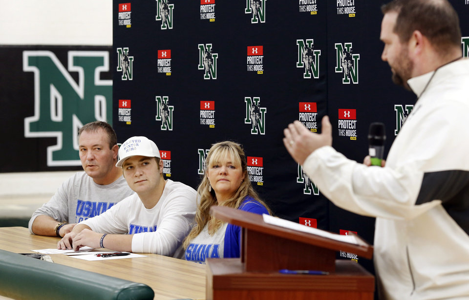 Photo - Bo Kemmet  sits between his parents as they listen to remarks about Kemmet's high school career before he signs to play football with United States Merchant Marines Academy during signing Day event at Norman North High School on Wednesday, Feb. 6, 2019.  Photo by Jim Beckel, The Oklahoman.