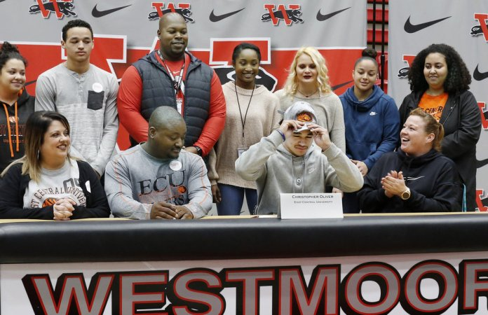 Photo - Christopher Oliver puts on a baseball cap after signing letter with East Central University during Signing Day event at Westmoore High School on Wednesday, Feb. 6, 2019.  Photo by Jim Beckel, The Oklahoman.