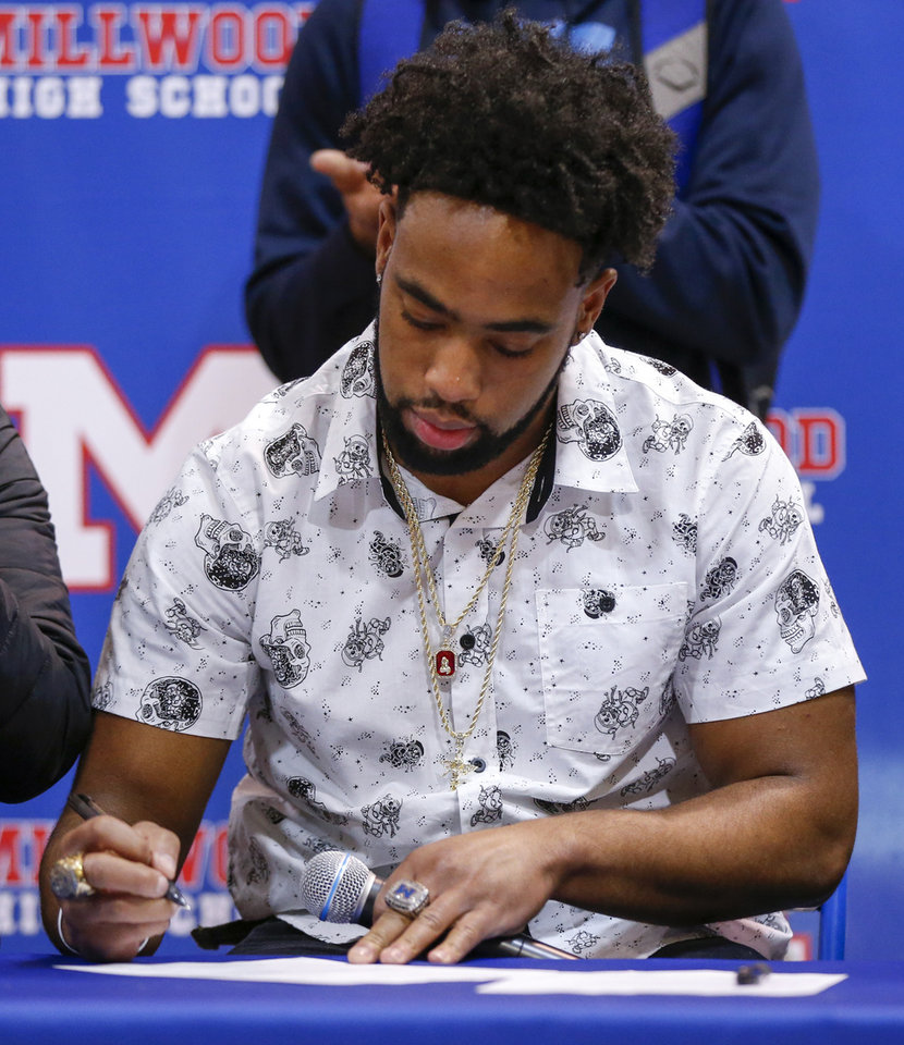 Photo - Millwood's Alijah Brison signs to play football at SWOSU during the signing ceremony for high school football players in the Millwood Field House in Oklahoma City, Wednesday, Feb. 6, 2019. Photo by Nate Billings, The Oklahoman
