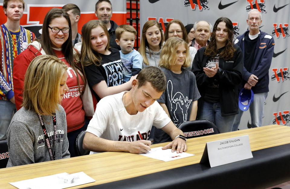 Photo - Jacob Vaughn signs his name to letter during Signing Day event at Westmoore High School on Wednesday, Feb. 6, 2019.  Photo by Jim Beckel, The Oklahoman.