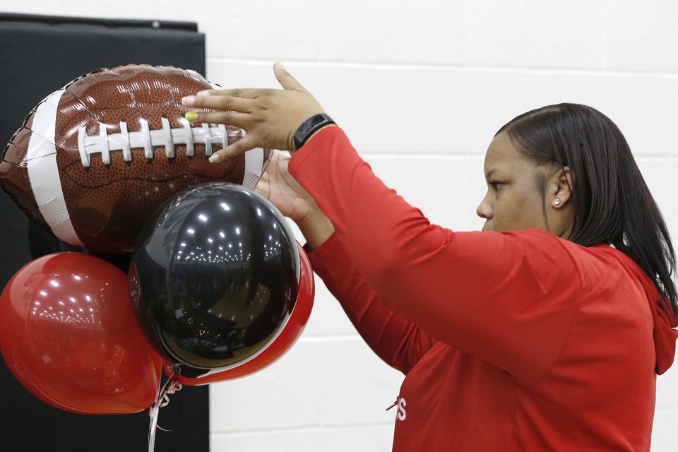 Photo - The mother of Ja'Vion Combs straightens a balloon bouquet at the reception table where her son, senior Ja'Vion Combs, would greet classmates and family after he signed letter to play football with Northwestern Oklahoma State University during Signing Day event at Norman North High School on Wednesday, Feb. 6, 2019.  Photo by Jim Beckel, The Oklahoman.