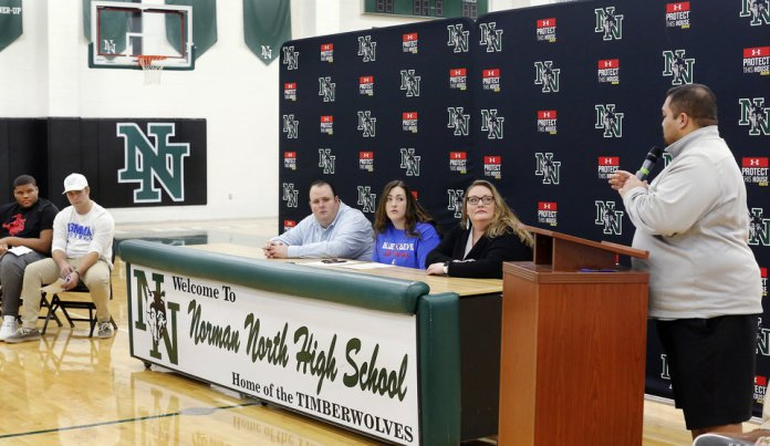 Photo - Alex Martin is seated at the signing table with her parents during Signing Day event at Norman North High School on Wednesday, Feb. 6, 2019. Martin signed to play softball at Kansas City Kansas Community College. Photo by Jim Beckel, The Oklahoman.