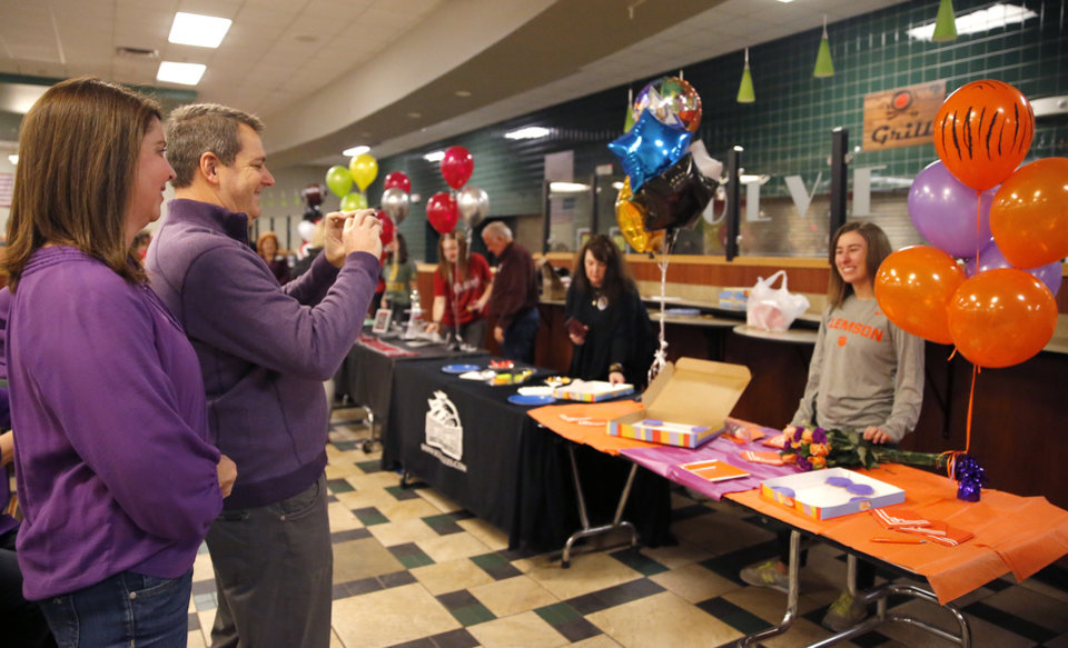 Photo - Mike O'Keefe takes a picture of his daughter, Catherine, after she signed with Clemson rowing as mom Lisa looks on during signing day ceremony at Edmond Santa Fe High School in Edmond, Okla., Wednesday, Feb. 6, 2019. Photo by Sarah Phipps, The Oklahoman