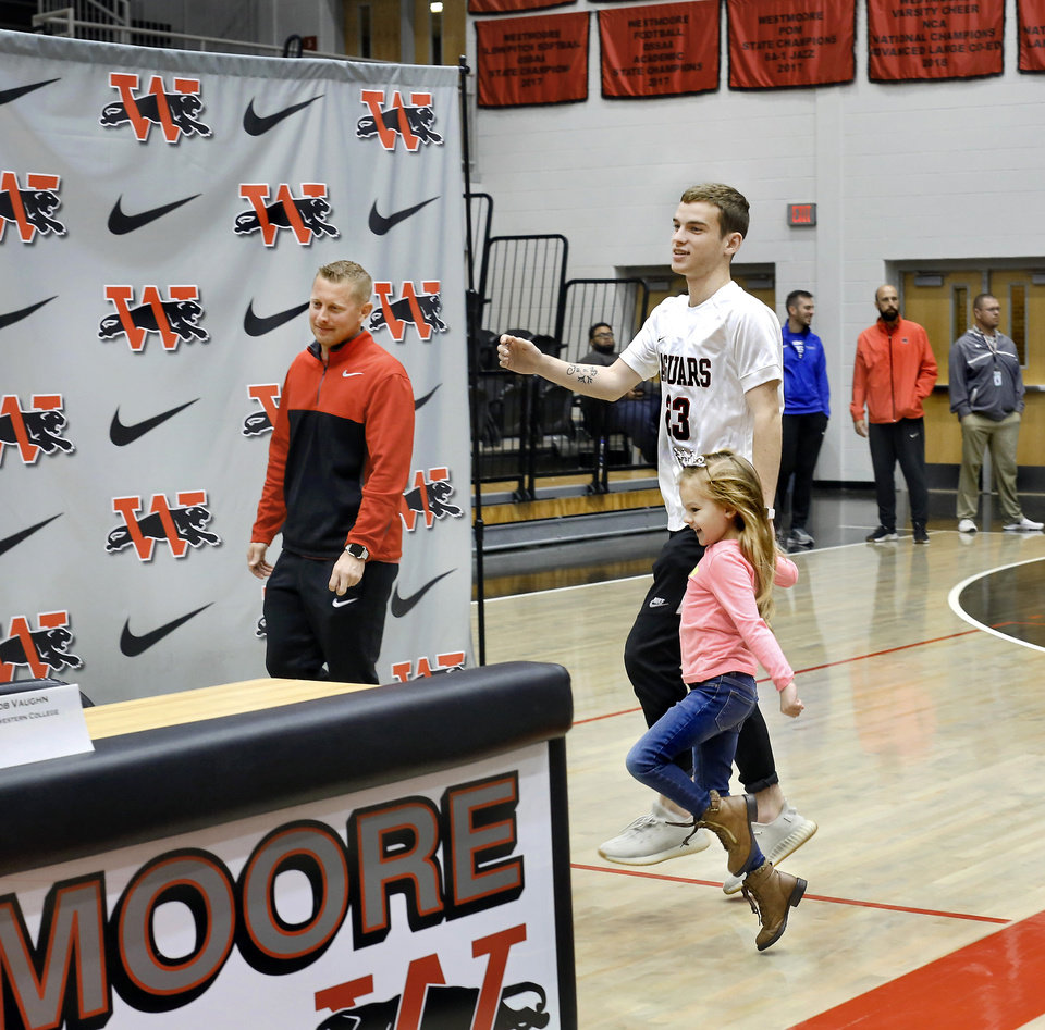 Photo - Jacob Vaughn is led to the signing table by his cousin, Brinley Vaughn, who held Jacob's hand as they skipped across the gym floor before being joined by other family members who witnessed the Westmoore senior place his signature to a letter during Signing Day event at Westmoore High School on Wednesday, Feb. 6, 2019. Brinley Vaughn celebrates her sixth birthday on Thursday.  Photo by Jim Beckel, The Oklahoman.