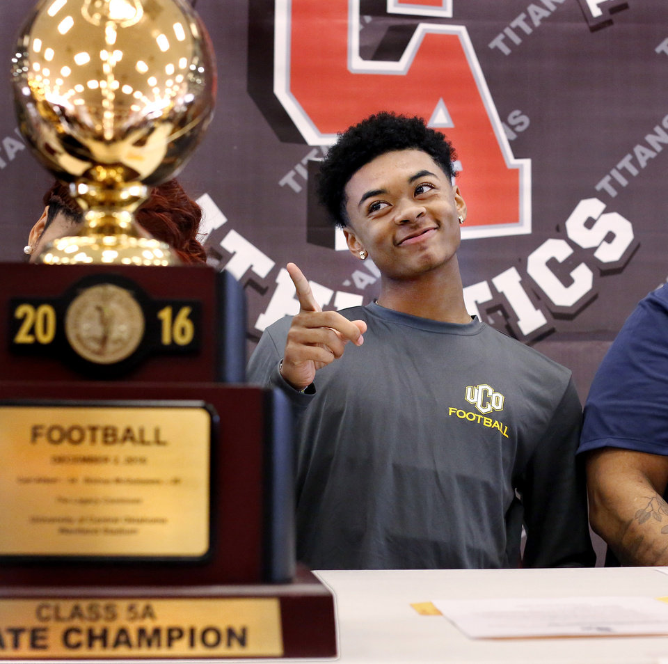 Photo - Titans senior Anthony Davis spots a friend in the crowd and gestures after he signed letter to play at UCO during Signing Day ceremony at Carl Albert  High School on Wednesday, Feb. 6, 2019.  Photo by Jim Beckel, The Oklahoman.