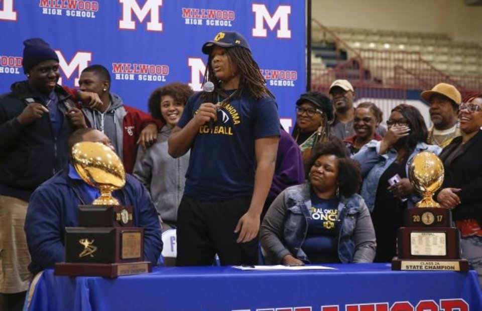 Photo -  Millwood's Isaiah Major speaks surrounded by his family during the signing ceremonyWednesday. Major will play football at UCO. [Photo by Nate Billings/The Oklahoman]