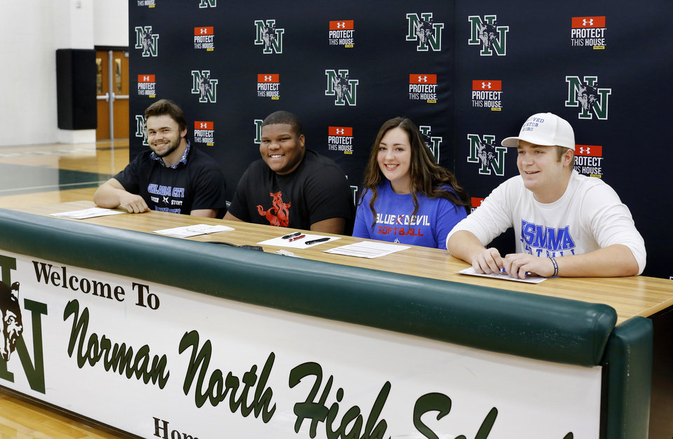 Photo - Athletes sit together briefly for a group photo after they signed individual letters to play at various schools during Signing Day event at Norman North High School on Wednesday, Feb. 6, 2019, are, from left, Blake Yohn (Track/Cheer),  Ja'Vion Combs (football),  Alex Martin (softball), and Bo Kemmet (football).  Photo by Jim Beckel, The Oklahoman.