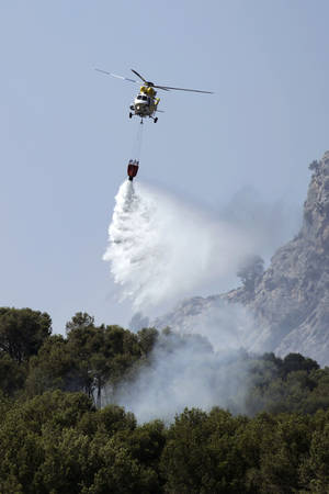Photo - A helicopter works above a fire, near the village of Andratx on the Spanish Balearic island of Mallorca, Spain, Sunday, July 28, 2013. The regional government of Spain's Balearic Islands says a wildfire is raging out of control in Mallorca, the popular Mediterranean luxury tourist destination. A statement says some 700 residents had to be evacuated early Sunday morning from the village of Estallencs as fires fanned by winds spread eastward along wooded hills. (AP Photo/Manu Mielniezuk)