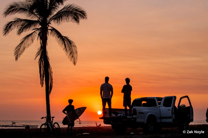 Image of surfers on the beach at sunset by Zak Noyle.