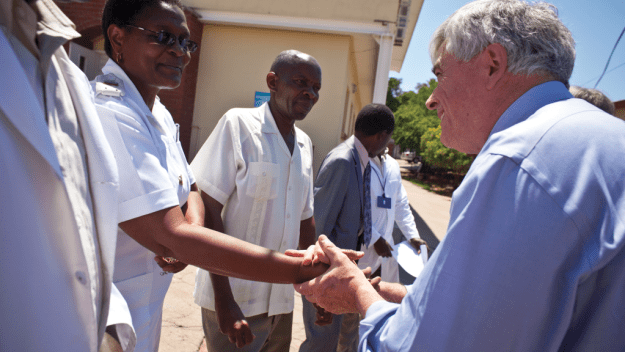Dr. Max Essex greets the staff at a clinic in Botswana.