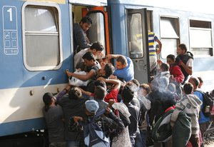 Migrants struggle to board a train at the railway station in Budapest, Hungary, Thursday, Sept. 3, 2015.