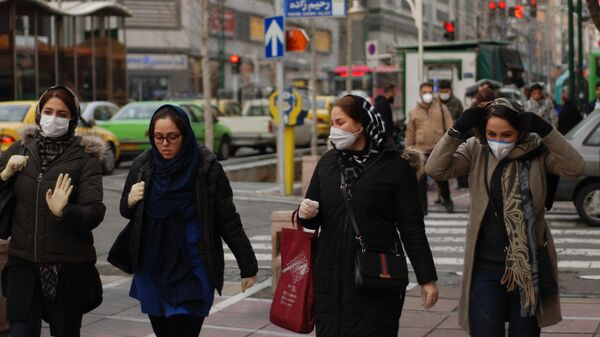 Tehran residents walk along one of the central streets wearing medical masks