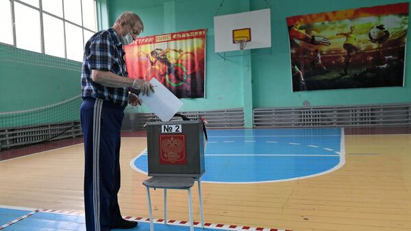 A man takes part in the vote on amendments to the Constitution of the Russian Federation at polling station No. 4 in the gym of a secondary school in the city of Divnogorsk, Krasnoyarsk Territory