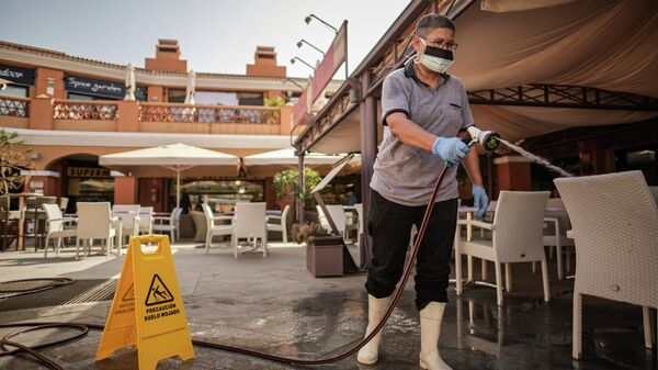 A masked employee washes the terrace of a shopping center in La Caleta, Tenerife