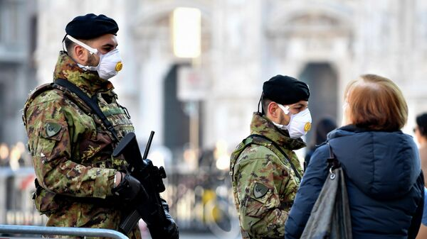Italian soldiers in sanitary masks patrol a square in central Milan
