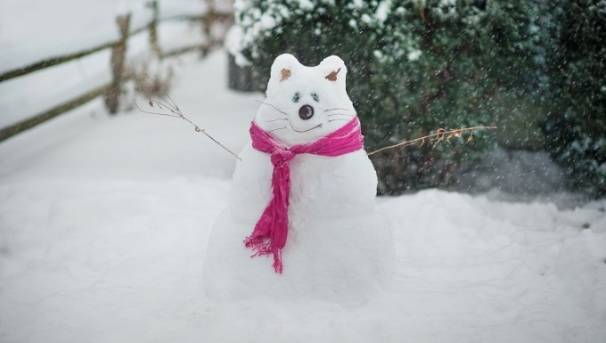A snowman made in the shape of a cat.