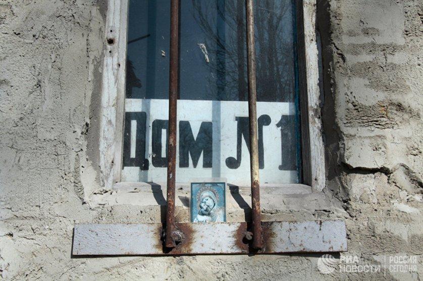 Икона в окне дома на улице Привокзальной в прифронтовом поселке Донецк-Северный в Донецкой области